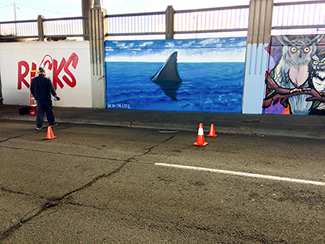 Photo of a local urban artist painting a mural under the I-70 viaduct during the 'duct-work Event.